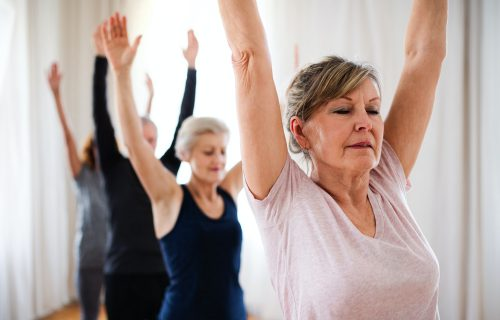 Group of senior people doing yoga exercise in community center club