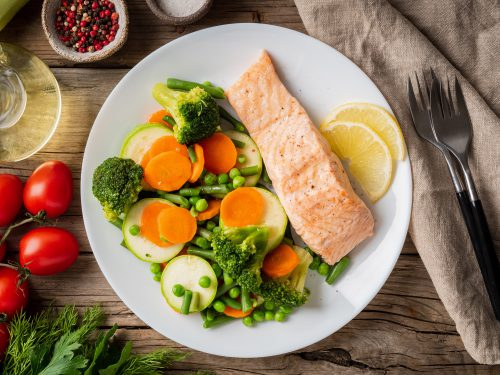 Steam salmon and vegetables, Paleo, keto, fodmap diet. White plate on old rustic wooden table,
